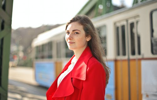 Woman in Red Blazer Standing Near White and Blue Train