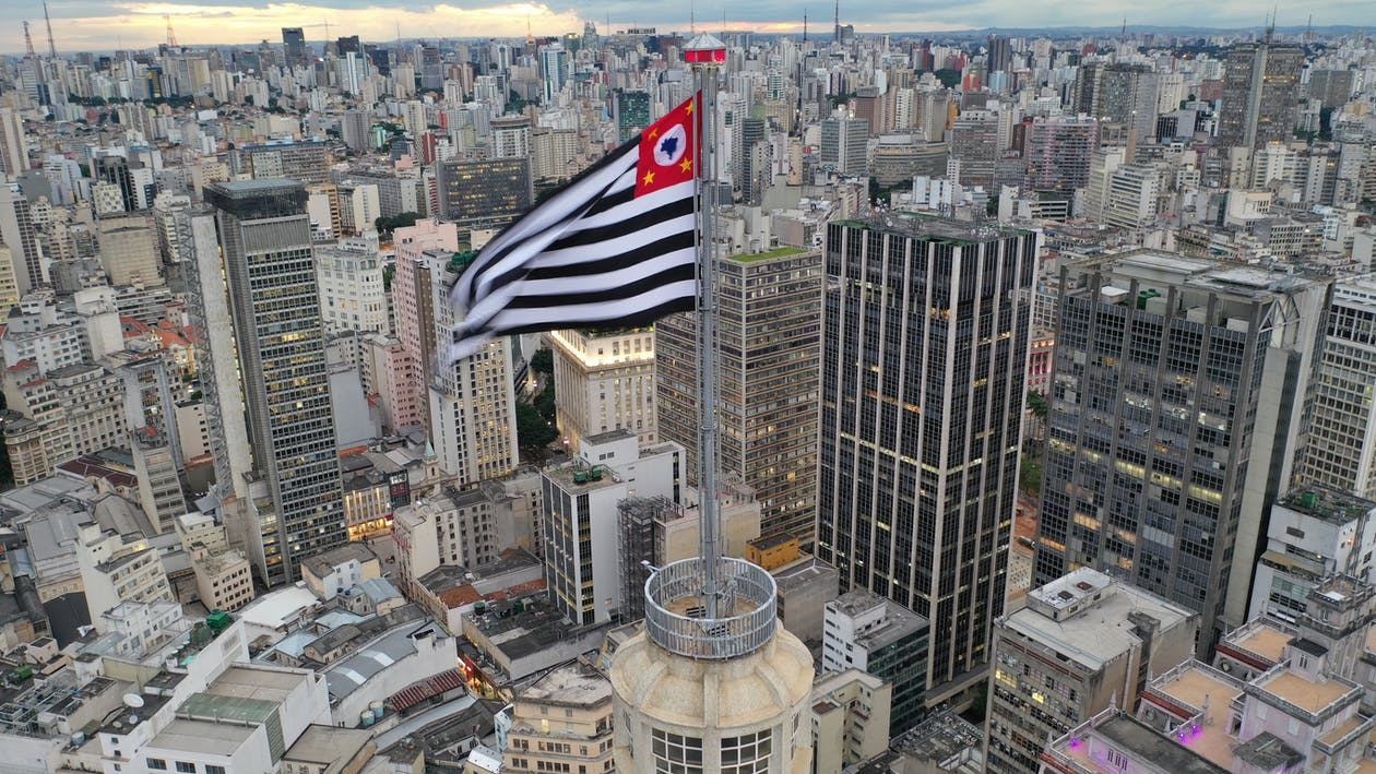 Aerial view of Sao Paolo flag waving on wind on skyscraper spire in urban metropolis district in daylight