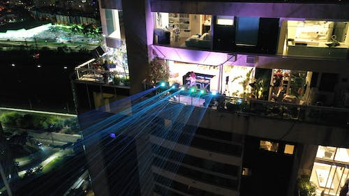 Modern skyscraper with glowing laser projectors at night