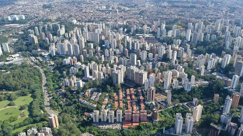 Aerial view of cityscape of modern district with tall buildings and green park at daytime