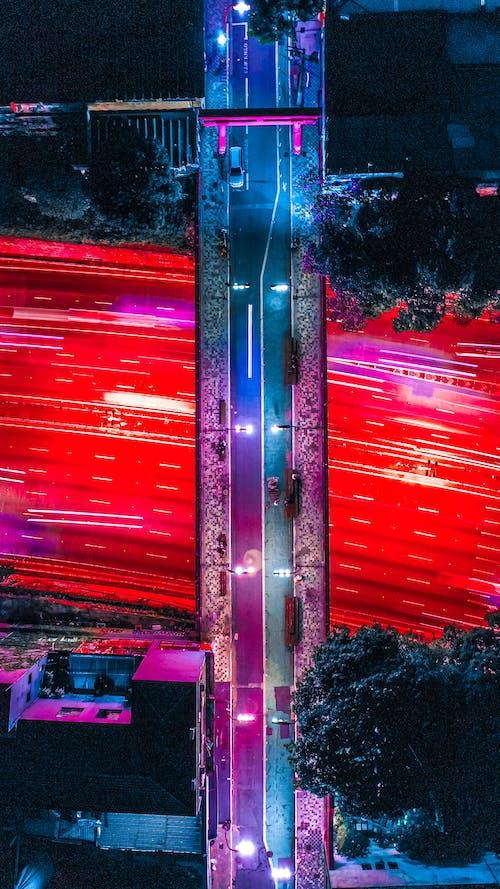 Long exposure of city traffic and bright illuminated overpass bridge at night time