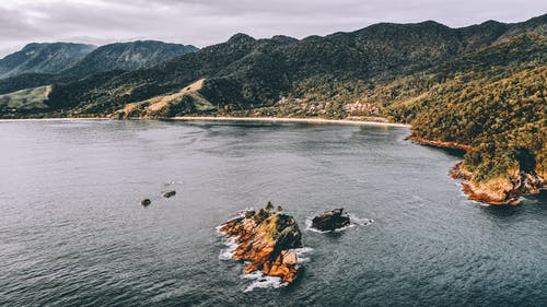 Aerial view of rippling ocean washing rocky shore with green hills at daytime