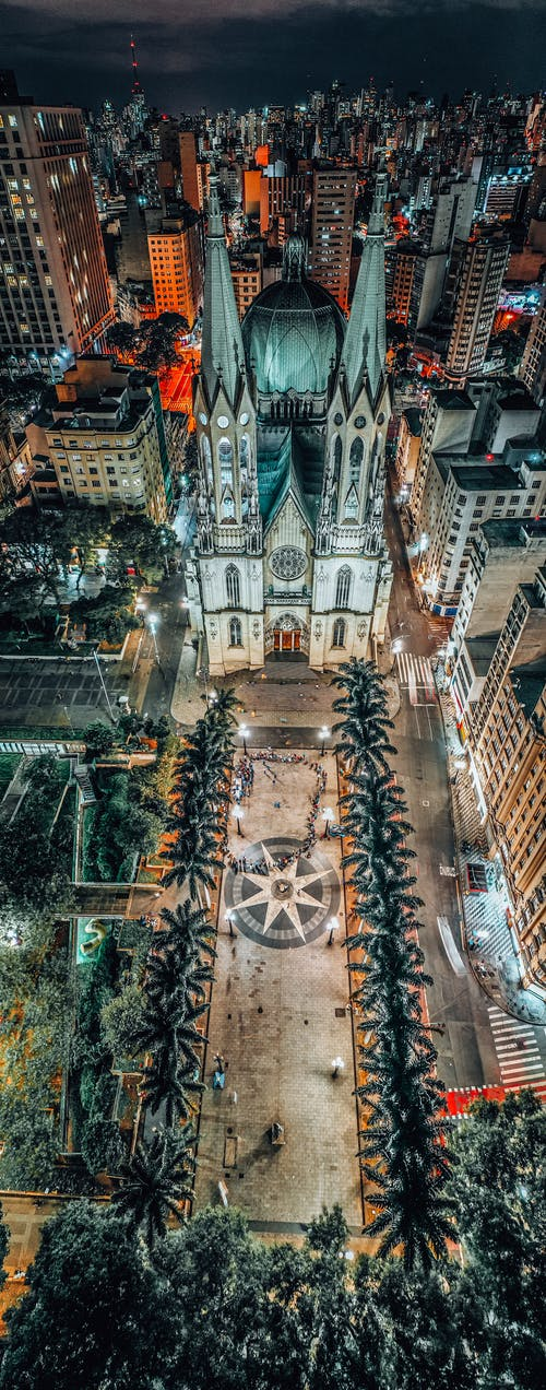 Aerial view of old Gothic church facade behind modern dwelling buildings in city at night