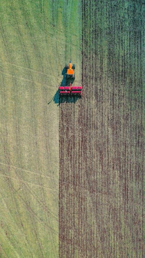 Modern tractor plowing green field