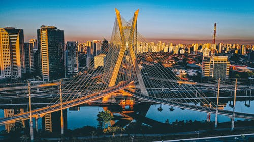 Modern bridge over calm river with reflected surface located against contemporary buildings in city center in Brazil in Sao Paolo