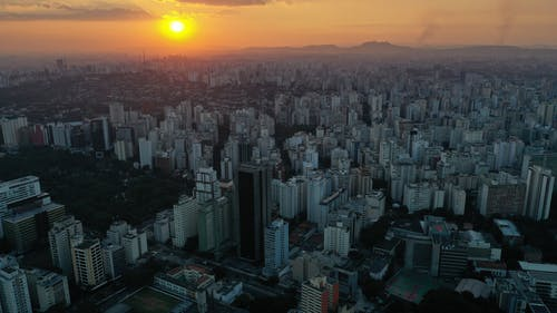 Aerial view of city with high rise buildings in residential districts illuminated by sunlight under colorful sky at sunrise