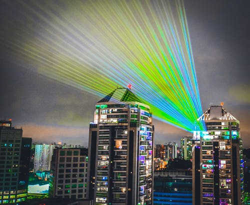High rise building illuminating street and sky by bright colorful lights in cloudy day in night time