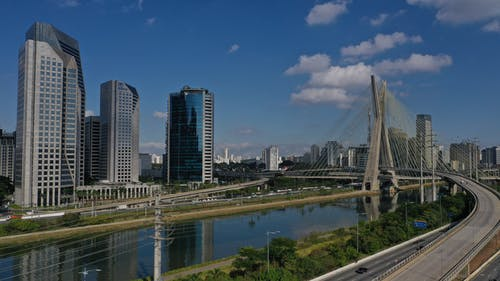 Contemporary city with skyscrapers and buildings near river and bridge