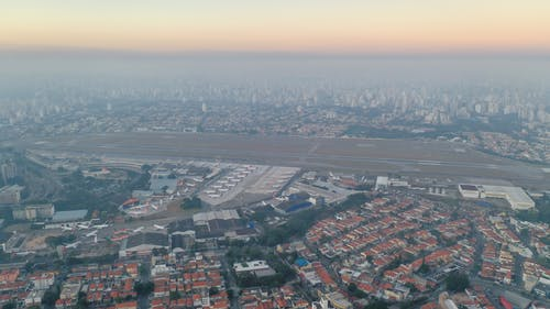 Cityscape with buildings and houses near roads and air strips