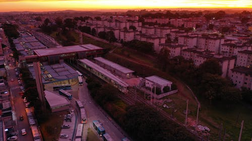 Drone view of town with aged tall residential buildings in bright shiny sunset
