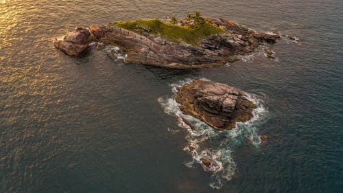 Drone view of rough rocky formation covered with green moss surrounded with sparkling water of ocean