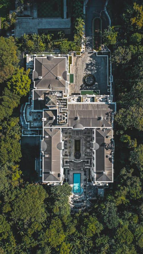 Drone view of contemporary house near trees with bright fresh verdant foliage in daytime