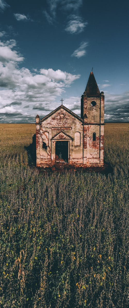 Exterior of old catholic church in green field under blue cloudy sky in summer