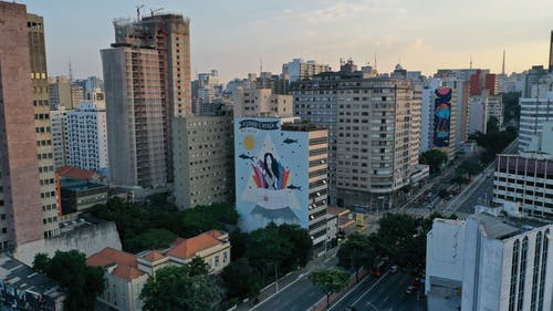 Cityscape of megapolis district with high dwelling houses with graffiti located along road with cars