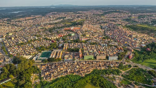 Aerial view of dwelling houses of residential district located among green trees in vast terrain