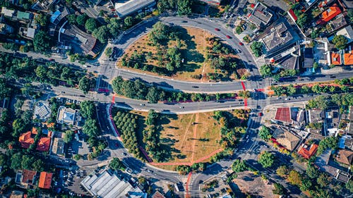 Drone view of cars driving on asphalt roundabout road crossed by straight roads in among residential buildings and trees