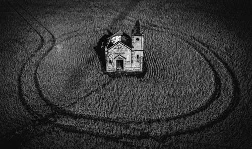 Small damaged church with cross in field
