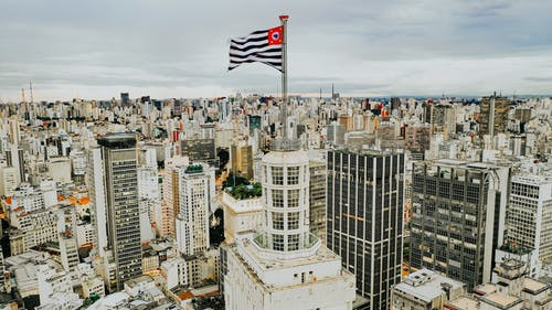 Waving flag placed on roof of multistory house located on street amidst contemporary buildings in city against cloudy sky in Brazil