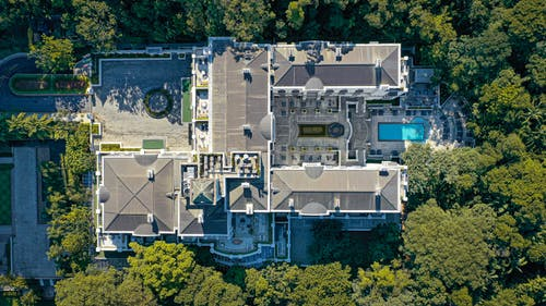 Aerial view of luxury expensive villa with pool located in wild place surrounded by lush trees