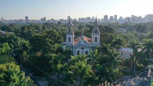 Breathtaking aerial view of old stone church located in green area of big city