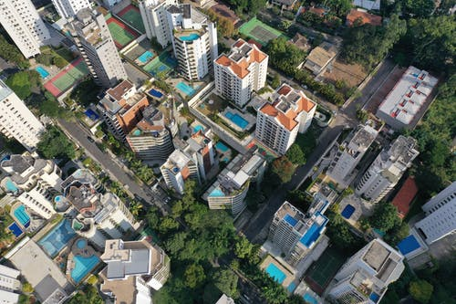 Drone view of contemporary tall apartment buildings located in residential city area amidst lush greenery in daylight