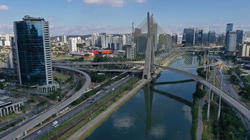 Futuristic cable stayed bridge over modern city canal