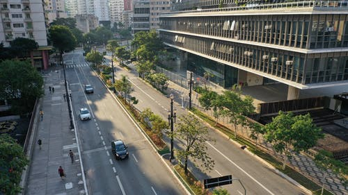 Contemporary city street with modern buildings and cars driving on road on sunny day