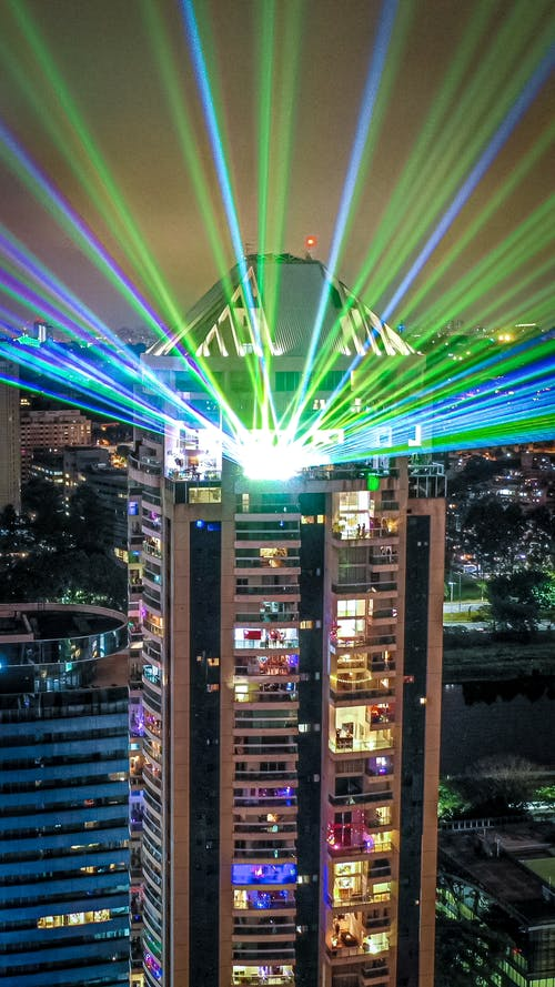 Bright colorful spotlights illuminating roof of multistory complex in modern megapolis at night