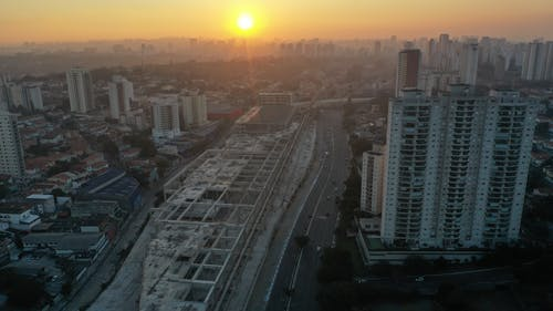Drone view of concrete beams of building under construction located along road with cars in town at sunset