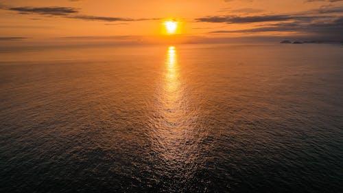 Rippling sea under bright orange sky at sunset
