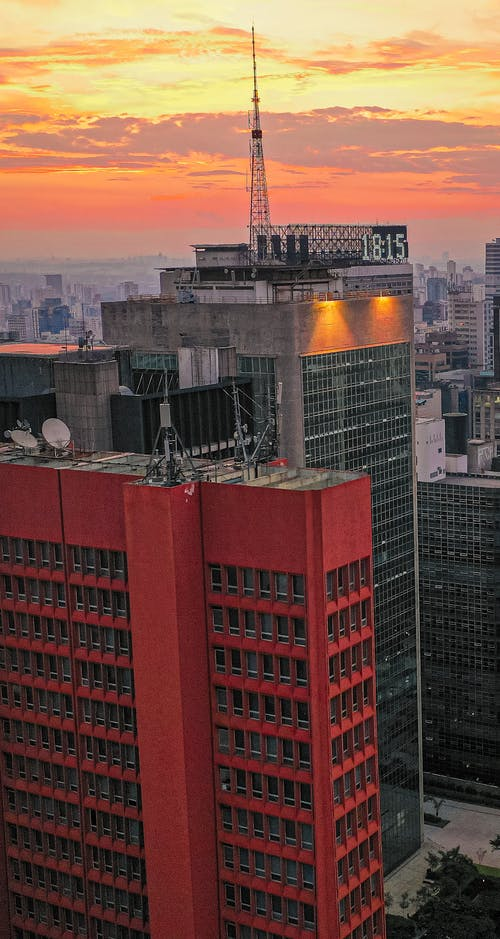 High skyscrapers located in modern megapolis district under colorful sunset sky with clouds at dusk