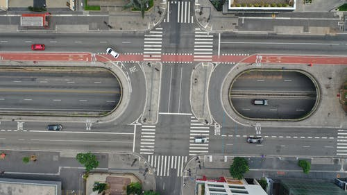 Drone view cars driving on large modern asphalt road with pedestrian crossing in daytime