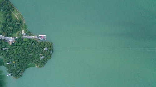 Drone view of calm green water of river washing island covered with green trees in daytime