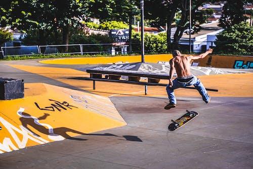 Anonymous man doing tricks on skateboard near ramp