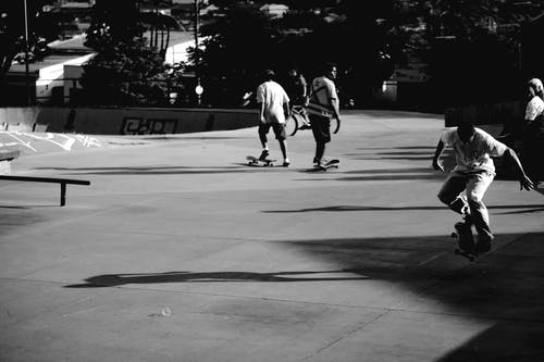 Black and white men practicing skateboarding on ramp in skate park at spare time