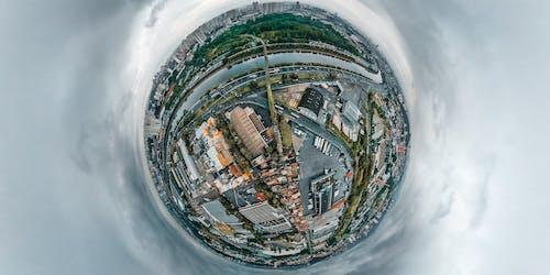 Fish eye view of storage buildings located in industrial zone on coast of river crossed by bridge