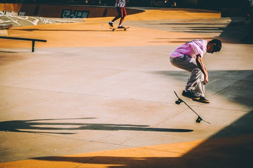 Side view of man doing trick on skateboard while practicing extreme hobby in skate park in sunny day