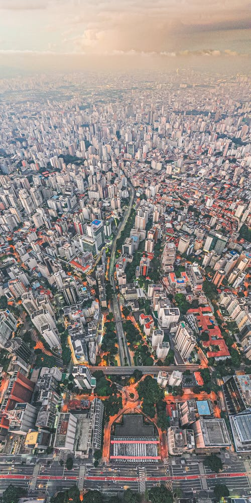 Aerial view of modern city with high rise residential buildings under cloudy sky in sunny day
