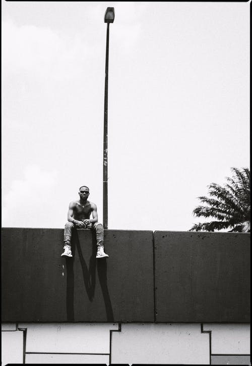 Black and white full length African American male with naked torso sitting on tall stone fence and looking at camera