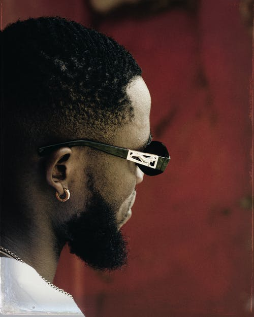 Side view crop unemotional African American male wearing trendy sunglasses and earring standing against weathered red wall