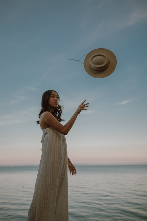 Calm ethnic female throwing hat while standing in sea