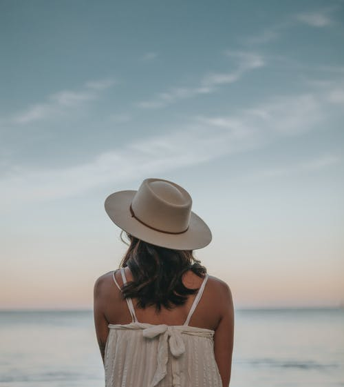 Back view of anonymous female enjoying view of calm sea under bright sky at sundown