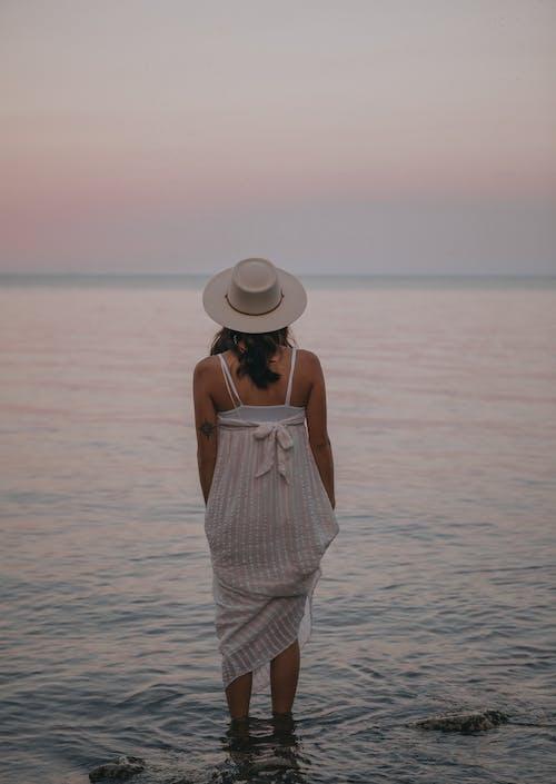 Romantic woman standing in water of sea
