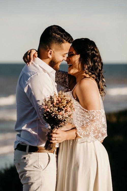 Loving newlyweds hugging and having fun on seashore