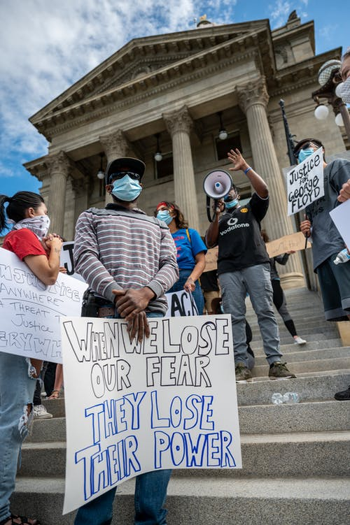 From below group of multiracial activists wearing respirators and holding placards and megaphone while attending rebel meeting near city government building