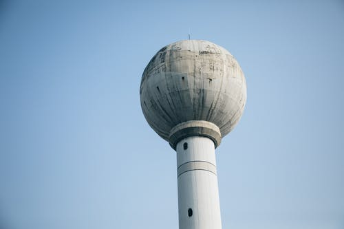 From below of high aged tower with water tank on top under blue sky in town