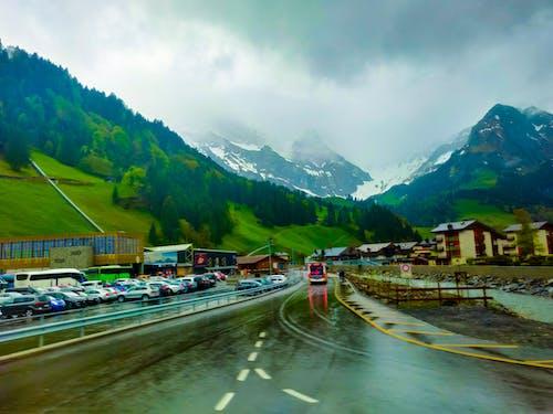 Ilmainen kuvapankkikuva tunnisteilla kaareva tie, lumihuippuiset vuoret, märkä tie, matkamuistoja