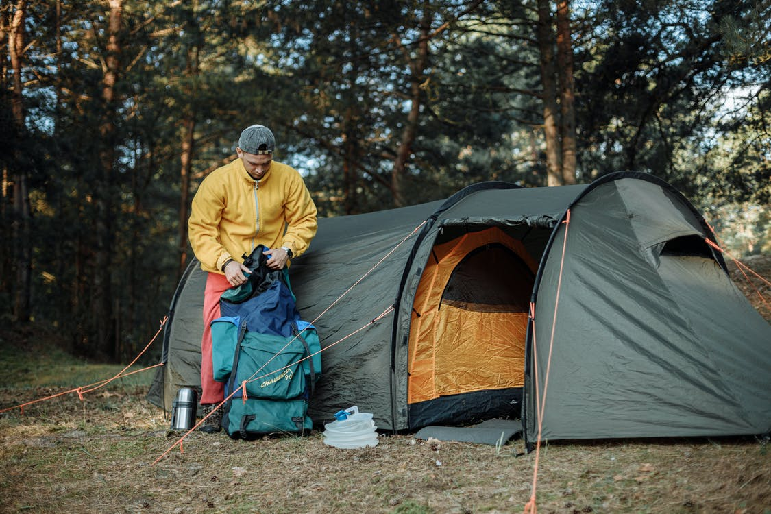 Man in Yellow Jacket and Blue Pants Standing Near Orange and Gray Dome Tent
