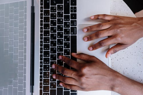 Persons Hand on Macbook Pro