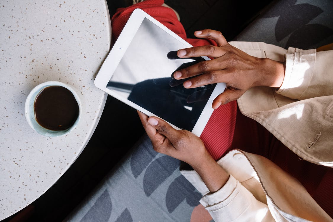 Person in White Long Sleeve Shirt Holding White Ipad
